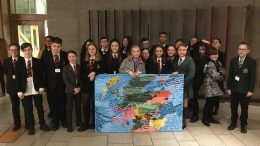 School pupils holding painted map of Scotland with UN Convention on the Rights of the Child inscribed on it