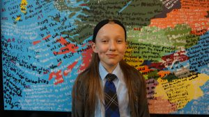 Pupil from St Paul's RC High School in front of map of Scotland decorated with extracts from the UN Convention on the Rights of the Child