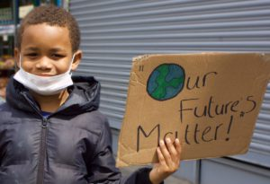 """Boy holding sign saying """"Our futures matter"""""""