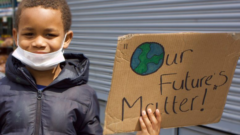 "Boy holding sign saying ""Our futures matter"""